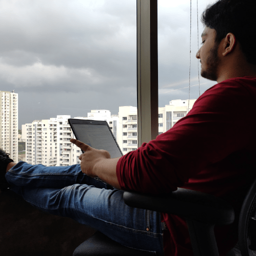 Man at sitting in front of a window viewing his tablet