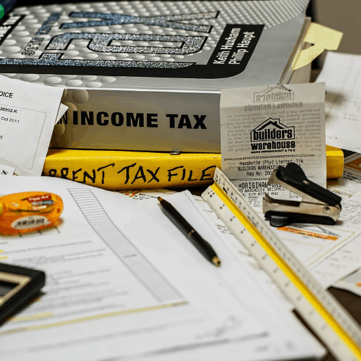 cluttered desk filled with tax paperwork and books