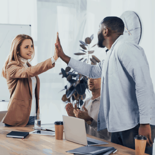 Two coworkers high-fiving in celebration